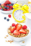 Breakfast with granola, fresh berries, milk, yellow alarm clock Royalty Free Stock Photo