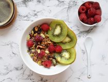 Breakfast granola with fruits Healthy eating concept. Home made granola with chia seeds, kiwi and raspberries on white marble background, top view Stock Photos