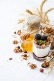 Breakfast - granola, yogurt, berries, nuts, honey, wheat. Breakfast - granola yogurt berries nuts honey wheat, white wood background Royalty Free Stock Photo