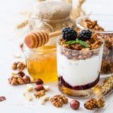 Breakfast - granola, yogurt, berries, nuts, honey, wheat. Breakfast - granola yogurt berries nuts honey wheat, white wood background Stock Photos