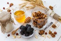 Breakfast - granola, yogurt, berries, nuts, honey, wheat. Breakfast - granola yogurt berries nuts honey wheat, white wood background Stock Photo