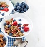 Breakfast with granola, yogurt and berries on white wooden table. Breakfast with granola, yogurt and berries on a white wooden table, closeup Royalty Free Stock Image