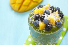 Breakfast green smoothie bowl topped with fruits Stock Images
