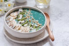 Breakfast spirulina coconut smoothie bowl topped with coconut flakes and berries Stock Photo