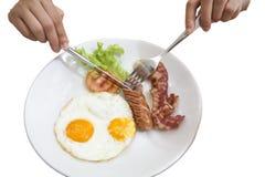Breakfast hand holding silverware focus sausage. Hand holding silverware eating sausage bacon, Eggs, Hash Browns, Toast, Orange Juice, water drink, silverware Royalty Free Stock Photography