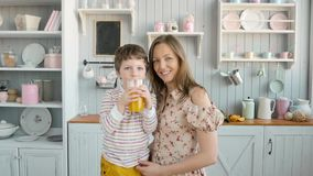 Breakfast for an happy american family, mom and little child boy with juice at kitchen stock footage