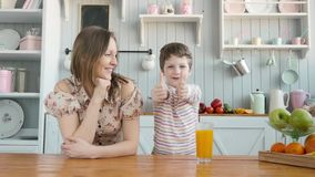 Breakfast for an happy american family, mom and little child boy at kitchen stock video