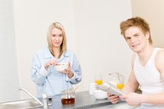 Breakfast happy couple eat cereal read newspaper Stock Photos