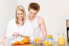 Breakfast happy couple make orange juice morning. Breakfast happy couple make orange juice in morning kitchen Royalty Free Stock Image