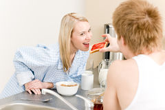 Breakfast happy couple man feed woman toast. Breakfast happy couple  man feed toast to woman in kitchen Stock Images
