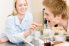 Breakfast happy couple woman feed man cereal Royalty Free Stock Images