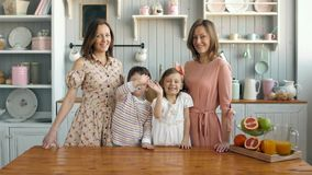 Breakfast for an happy family, sisters twins moms with two childs girl and boy morning stock video footage