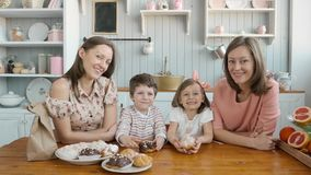Breakfast for an happy family, sisters twins moms with two childs girl and boy morning eating sweets desserts and fruits stock video