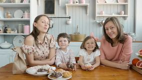Breakfast for an happy family, sisters twins moms with two childs girl and boy morning eating sweets desserts and fruits stock video footage