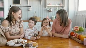 Breakfast for an happy family, sisters twins moms with two childs girl and boy morning eating sweets desserts and fruits stock footage