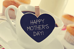 Breakfast and happy mothers day written in a heart-shaped blackb. The sentence happy mothers day written in a heart-shaped blackboard placed in a cup of coffee Stock Photo