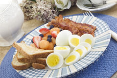 Breakfast with Hard Boiled Eggs. A sunny morning breakfast with hard boiled eggs, crispy bacon, fresh fruit and buttered toast, place setting with blue placemat Stock Image