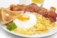 Breakfast Hash Browns Bacon Fried Egg Toast. Cooked breakfast of crisply fried bacon, fried egg sunny side up, hash brwons, toast and orange juice Stock Images