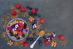 Breakfast Health Food. Concept with granola, pollen grain, fresh berry fruit, nuts and edible flowers High in antioxidants, anthocyanins, protein and vitamins Royalty Free Stock Images