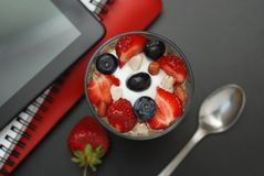 Breakfast for health, fresh strawberries, Blueberies, with oatmeal Black office table. Tablet, laptop and Notebook. Top view. Copy stock photos
