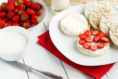Breakfast for health sandwiches from rice vegan waffle with Greek yogurt and fresh strawberries. On a white red background stock photography