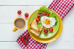 Breakfast with heart-shaped fried egg, toast, cherry tomato, let Royalty Free Stock Image