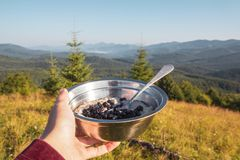 Breakfast in the hike, a bowl of porridge and berries in the female hand on the background of the morning mountain landscape royalty free stock photos