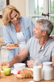 Breakfast at home. Smiling Woman Serves Breakfast To Her Husband In Morning Stock Photos
