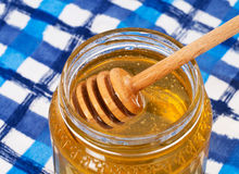 Breakfast honey on blue white tablecloth, with wooden dipper. Royalty Free Stock Photography