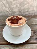 Breakfast, hot coffee with chocolate froth and a piece of marshmallow, on a wooden table royalty free stock photo