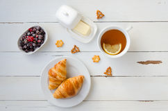 Breakfast from hot croissants, butter,tea and currants on wooden table. Flat lay. Breakfast from hot croissants, butter, tea with lemon, crackers, berries, black Stock Photos