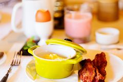 Breakfast in hotel. Delicious breakfast with scrambled eggs and bacon Royalty Free Stock Photo