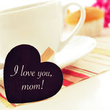 Breakfast and I love you mom written in a heart-shaped blackboar. The sentence I love you mom written in a heart-shaped blackboard placed in a cup of coffee Stock Photo