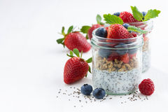 Breakfast in a jar, chia with berries and oat flakes on white. Table, closeup Stock Photography