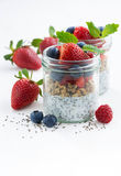 Breakfast in a jar, chia with berries and oat flakes. On white table, vertical, closeup Stock Photography