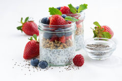 Breakfast in a jars, chia with berries and oat flakes. On white table, closeup, horizontal Stock Photos