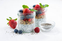 Breakfast in a jars, chia with berries and oat flakes. On white table, horizontal Stock Photo