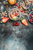 Breakfast in jars. Muesli with strawberries and other fresh berries, nuts and seeds on rustic background. Top view stock image