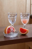 Breakfast Juice. Two goblets, one partially filled with juice. Pieces of grapefruit in front of goblets. One piece sitting on a juicer royalty free stock photos