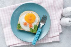 Breakfast for kids. Egg toast with funny cute food art. On a blue plate. Top view stock images