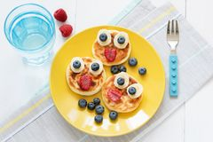 Breakfast for kids. Funny animal face pancakes on yellow plate. Breakfast for kids. Funny animal face pancakes with fresh berries on yellow plate and glass of stock photo