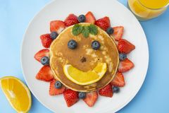 Breakfast for kids. Homemade american pancake sun, with fresh blueberries, strawberries and orange juice. Blue background stock photos