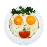 Breakfast for kids. Kids funny meal on white plate. Eggs, parsley vegetables/bread/ketchup is formed by a funny face on a white plate. The concept of food for Stock Image