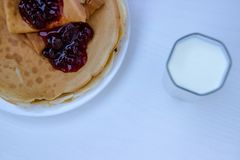 Breakfast for kids, pancakes with milk and jam royalty free stock images