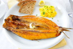 Breakfast Kippers. Fresh smoked kipper with scrambled egg and brown bread royalty free stock image