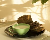 Breakfast on kitchen. Solar morning. On a black plate the fresh cut black bread and milk in a green mug. On a wall a shade from a window plant royalty free stock images