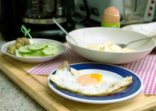 Breakfast in the kitchen. Fried eggs, boiled egg on a plate cucumbers and green olives, in the background of coffee on the table Royalty Free Stock Photos