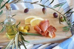 Breakfast in the kitchen with a jamon and stuffed olives, a bottle of olive oil and a twig with olives.  Royalty Free Stock Photography