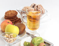 Breakfast.1. Kiwi, apples, cookies with a peanut, gingerbreads, juice, pistachios on the gray background Royalty Free Stock Image