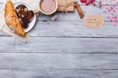 Breakfast, on the table, a croissant with a chocolate cake, on a gray background, a free place for text. Stock Photography